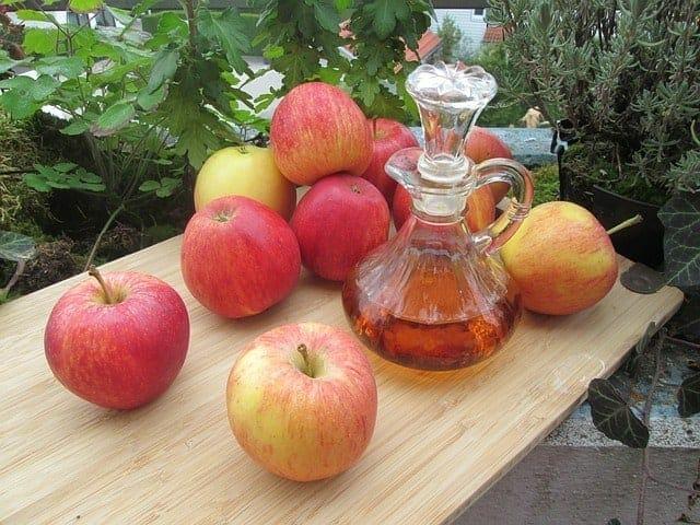 Färska äpplen och en flaska äppelcidervinäger på bordet.