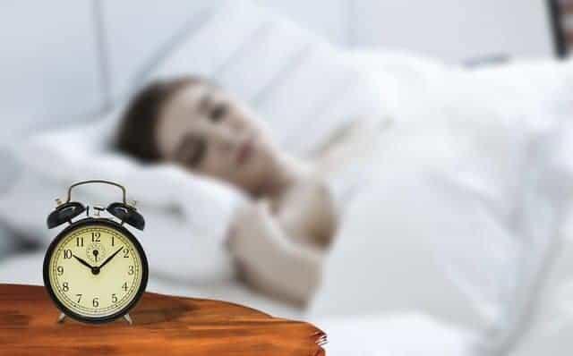 en kvinna som sover med en väckarklocka bredvid sin säng