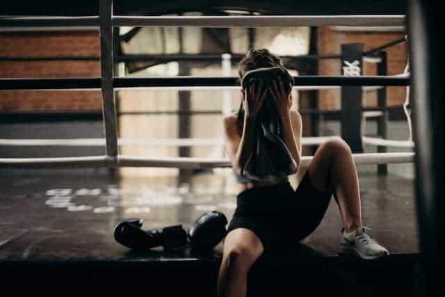 kvinna torkar svett från ansiktet efter ett ansträngande träningspass