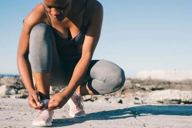 kvinna i sportkläder knyter sin sko