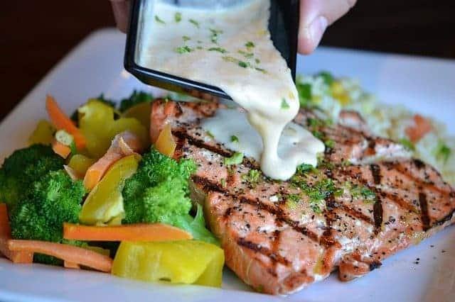 Grönsaker och bakad fisk på en tallrik