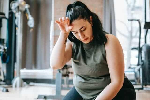 överviktig kvinna trött efter ett träningspass