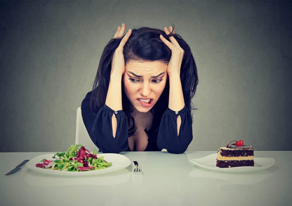 en kvinna sitter vid ett bord med en tallrik med tårta och en tallrik med sallad