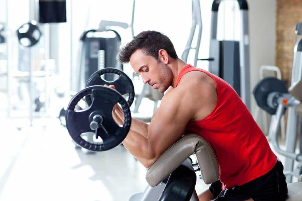 En man tränar med en skivstång på gymmet.