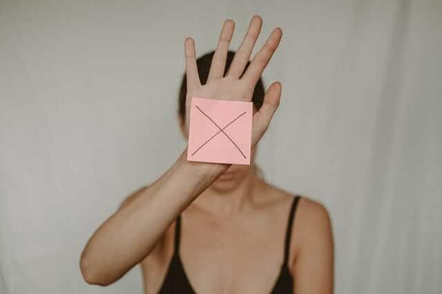 en ledsen kvinna håller en kartong med ett x framför sig